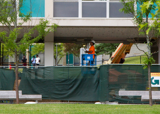 A construction worker puts finishing touches on the ceiling of the DellPlain Hall breezeway. Work is expected to be finished before students move-in for the fall semester. Photo taken Aug. 1, 2017